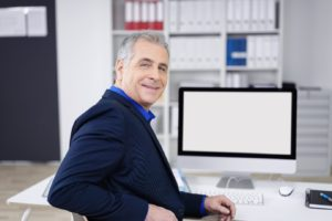 Older man at computer in office