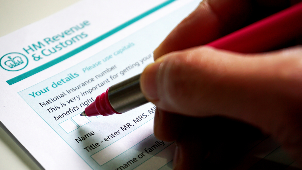Hand filling out HMRC form